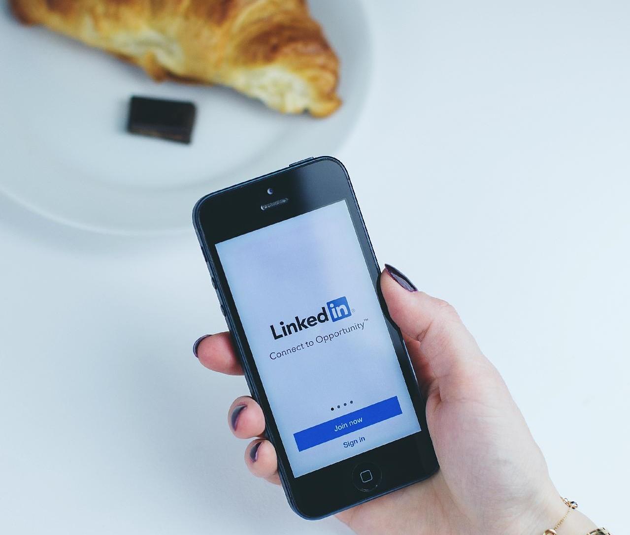 mano de mujer sujetando móvil dónde aparece inicio de linkedin. De fondo un croissant para desayunar.